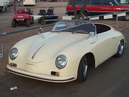 A replica of a cream 1955 Porsche Speedster, with other vehicles in the background.