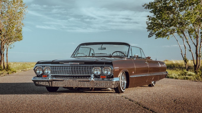Classic brown Impala convertible parked on the street under autumn trees