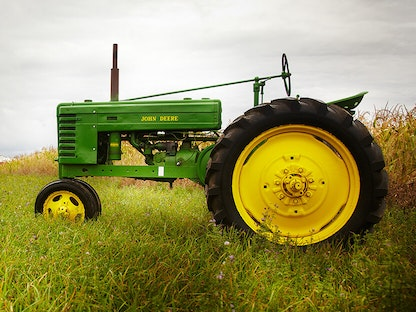 A green collector tractor parked in a field.