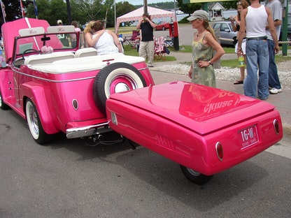 A pink collector vehicle and trailer parked on the side of the road, with passerby taking photos.