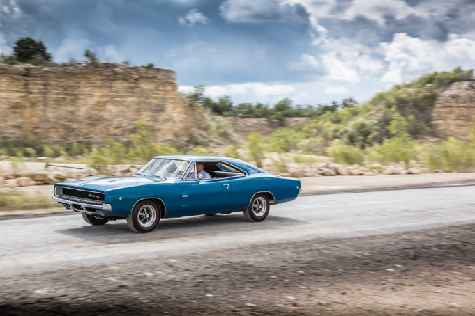 Blue classic Charger speeding down desert highway with trees in background