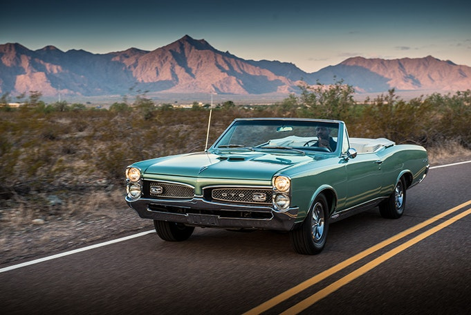 Classic green Pontiac GTO driving away from mountain sunset, three quarter view