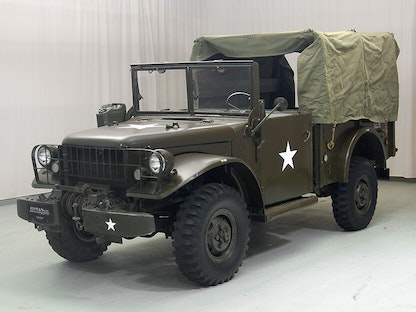 A collector military truck with a canvas cover, parked indoors.