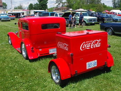 A red collector Coca-cola vehicle and trailer parked on grass in front of other collector vehicles.