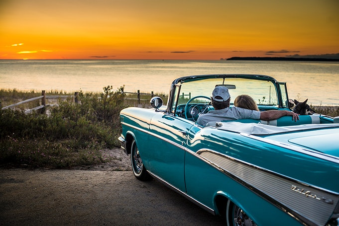 blue bel air car parked in front of sunset