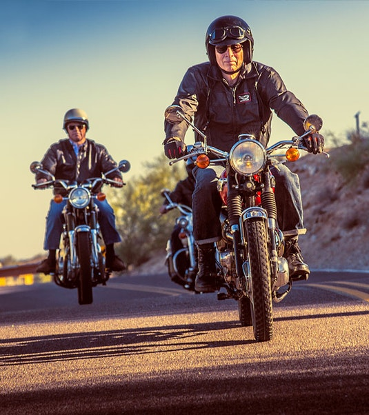 two classic collector motorcycles being driven down a road