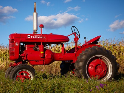 A red collector tractor parked in a field with blue sky in the background.