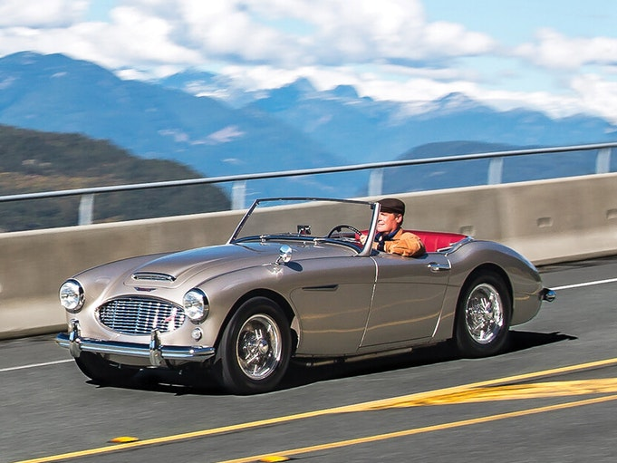 A man driving a collector car down a road, with mountains and blue sky in the background.