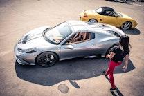 A woman walking to a silver Ferrari.