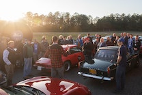 Group of people gathered around classic cars