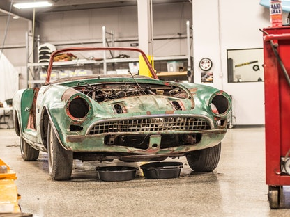 A green collector car without headlights, doors, or hood, being restored in a garage