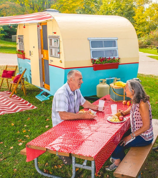 Two people picnicking in front of a vintage camper trailer