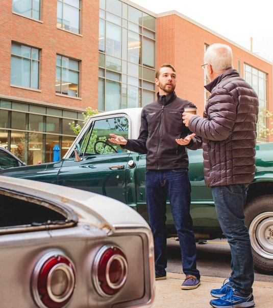 two men having a conversation next to two classic collector cars