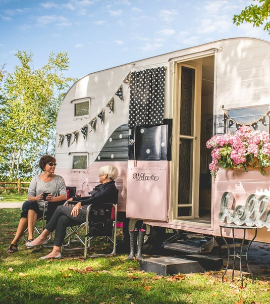 Two people sitting in front of a vintage camper trailer