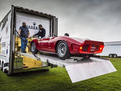 A red collector convertible being transported from a trailer.
