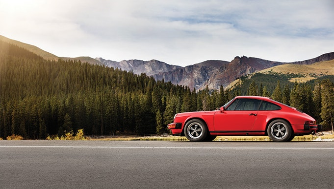 Red Porsche 911 parked on road, mountains in background
