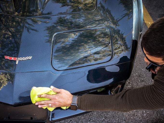 A man polishing his beloved, black Corvette.