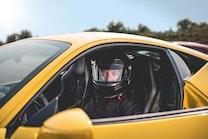 Driver sitting in a yellow 2013 Ferrari 458.