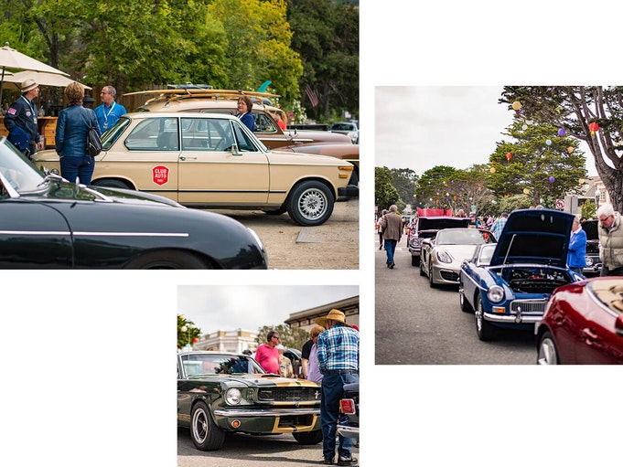 Streets lined with collector vehicles, popped hoods, and people partaking in a car club event.