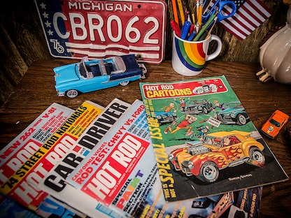 A stack of vintage magazines on a desk, with toy cars and a license plate in the background.