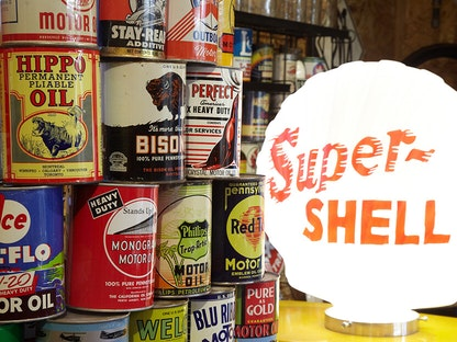 A stack of vintage oil cans by a lamp, with shelves of oil cans in the background.