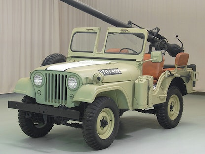 A green collector military jeep with a mounted gun, parked indoors.