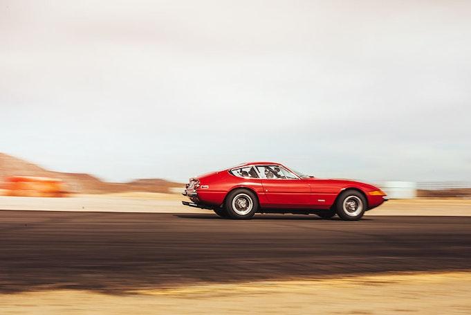 Red 1971 Ferrari driving down the road.