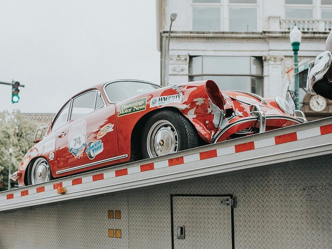 A red Porsche with a broken headlight and dented frame, being pulled up a trailer.