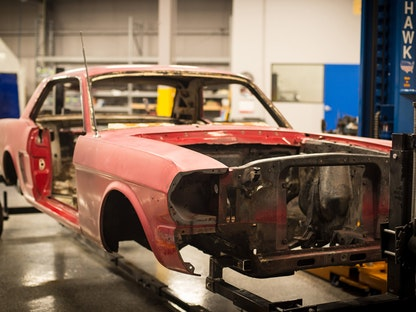A red collector car with just a frame and fender, being restored in a garage