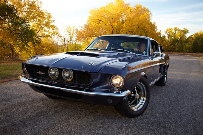 Black classic Mustang driving straight towards the camera with sunset in background