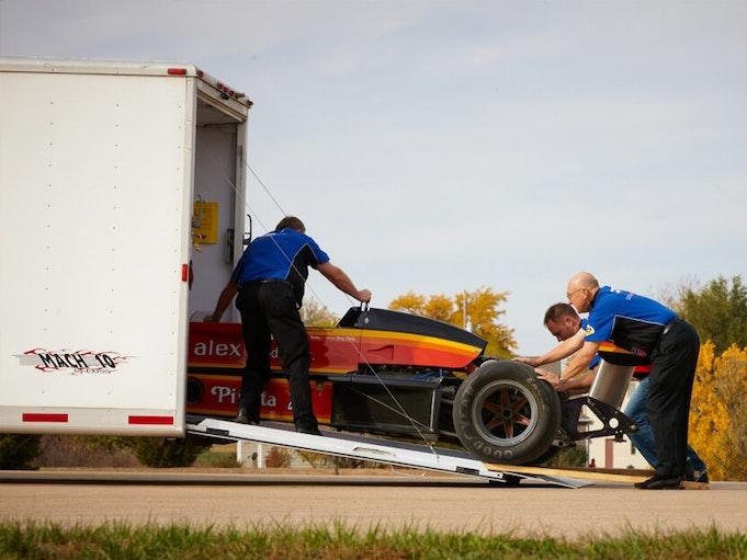 Three men pushing a collector race car into a trailer.