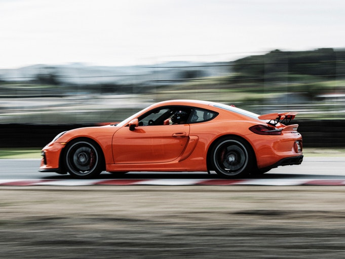 An orange collector car driving fast around a track.