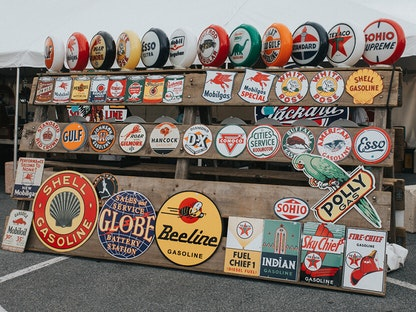 Vintage signs for beverages and car parts behind an array of antique collectibles like cans of axle grease and figurines.