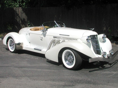 A replica of a white 2003 Auburn Speedster, parked in front of a fence.