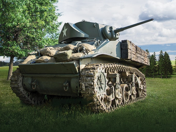 A collector military vehicle on a grassy lawn with blue sky in the background.