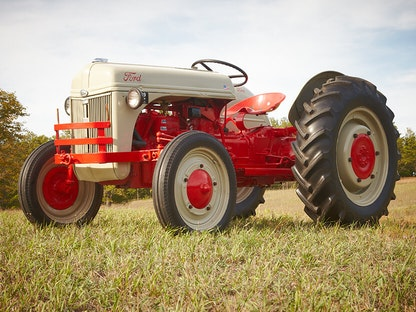 A cream and red collector tractor parked on a grassy lawn.
