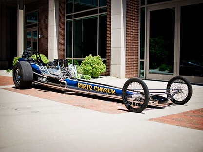 A long blue collector race car parked in front of a building.