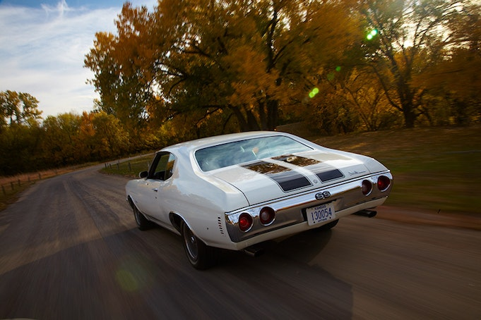 Back view of classic white Chevelle driving in to sunset