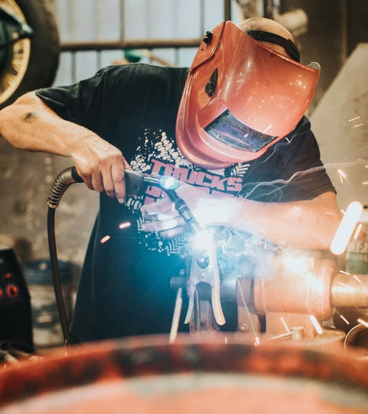 person in a repair shop wearing protective gear repairing or welding a part
