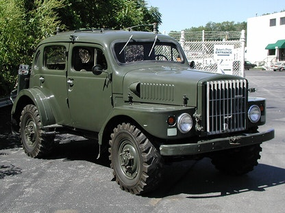 A dark green military vehicle in a parking lot, with bushes and a building in the background.