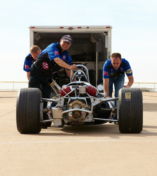 Three men pushing a collector race car, with a trailer in the background.